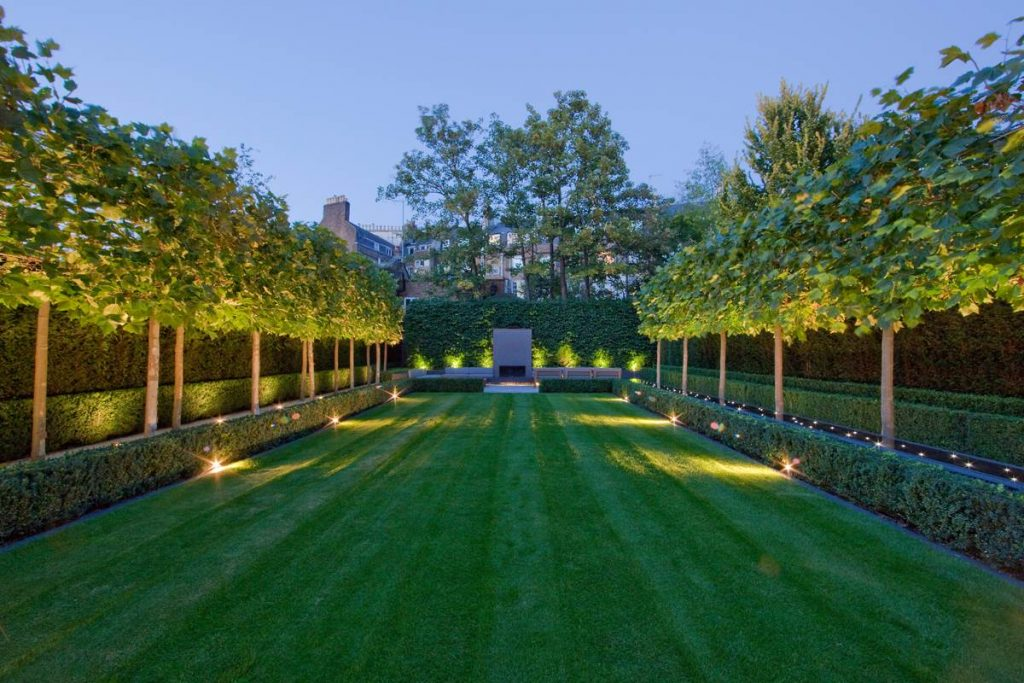 Well-kept garden at night outside Swiss Cottage home