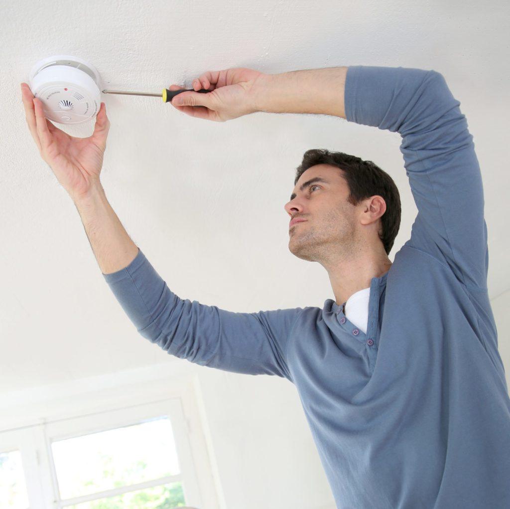 Man wearing blue jumper installing fire alarm system