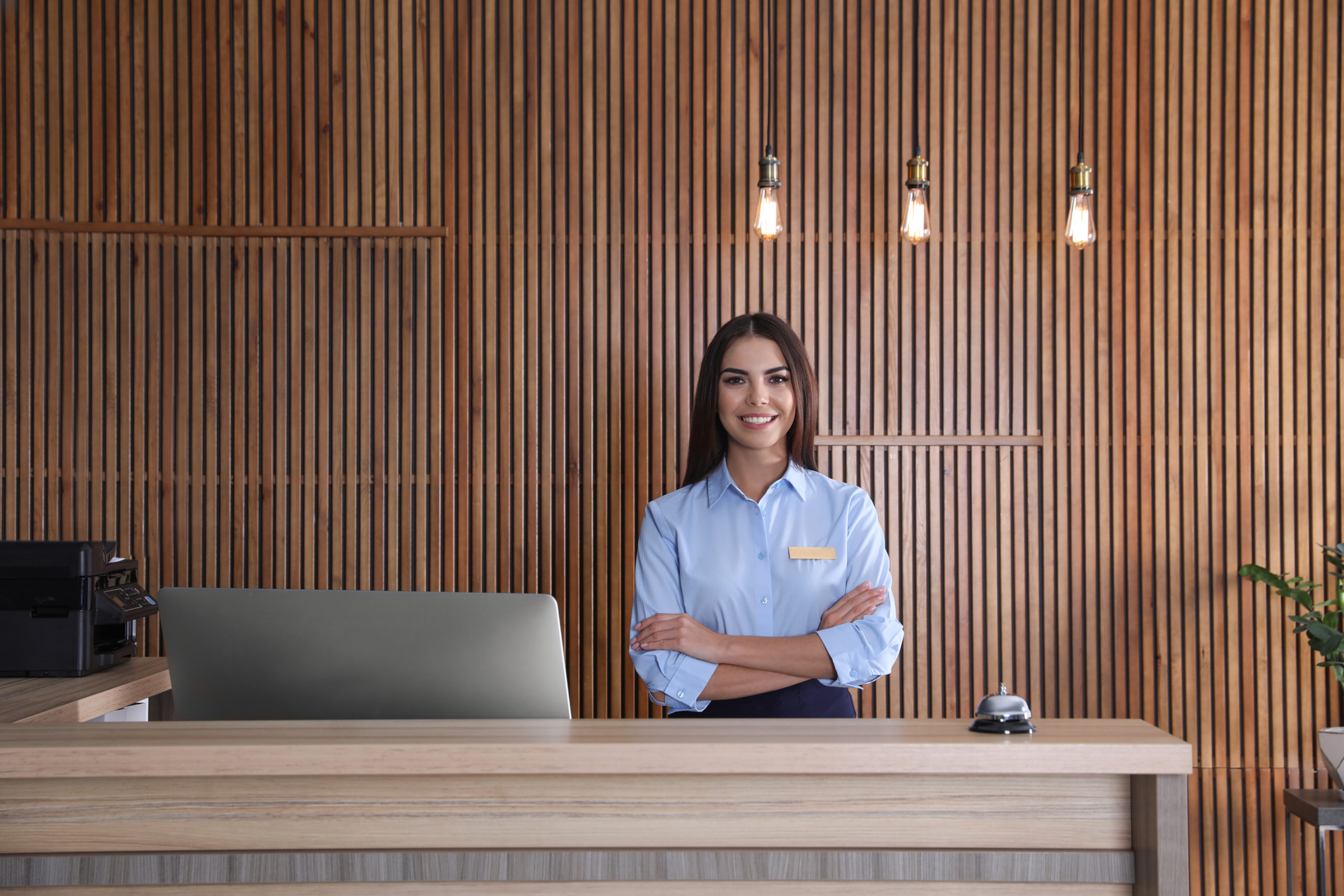 commercial-and-hospitality-Design-by-MDfx-woman-stading-at-hotel-reception-beautifully-designed-with-wooden-panel-