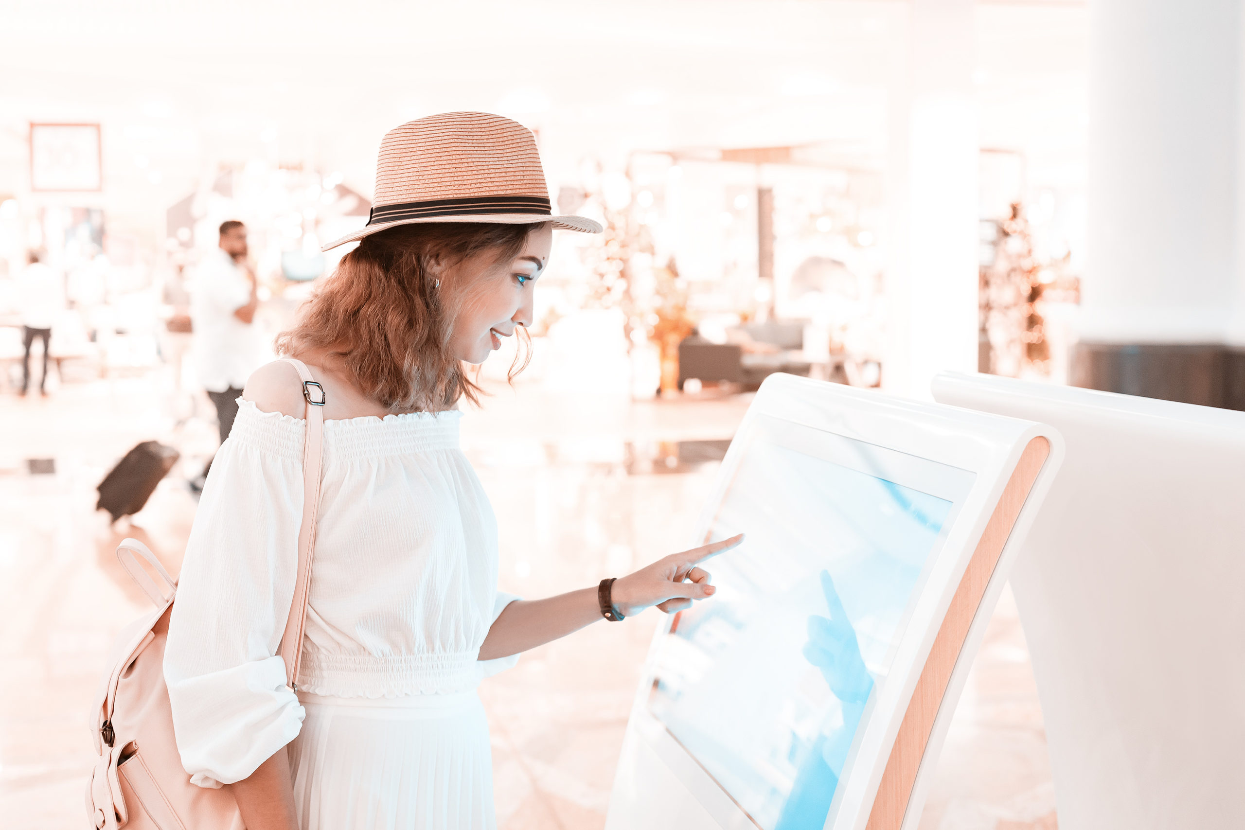 commercial-and-hospitality-Design-by-MDfx-woman-wearing-white-using-digital-kiosk