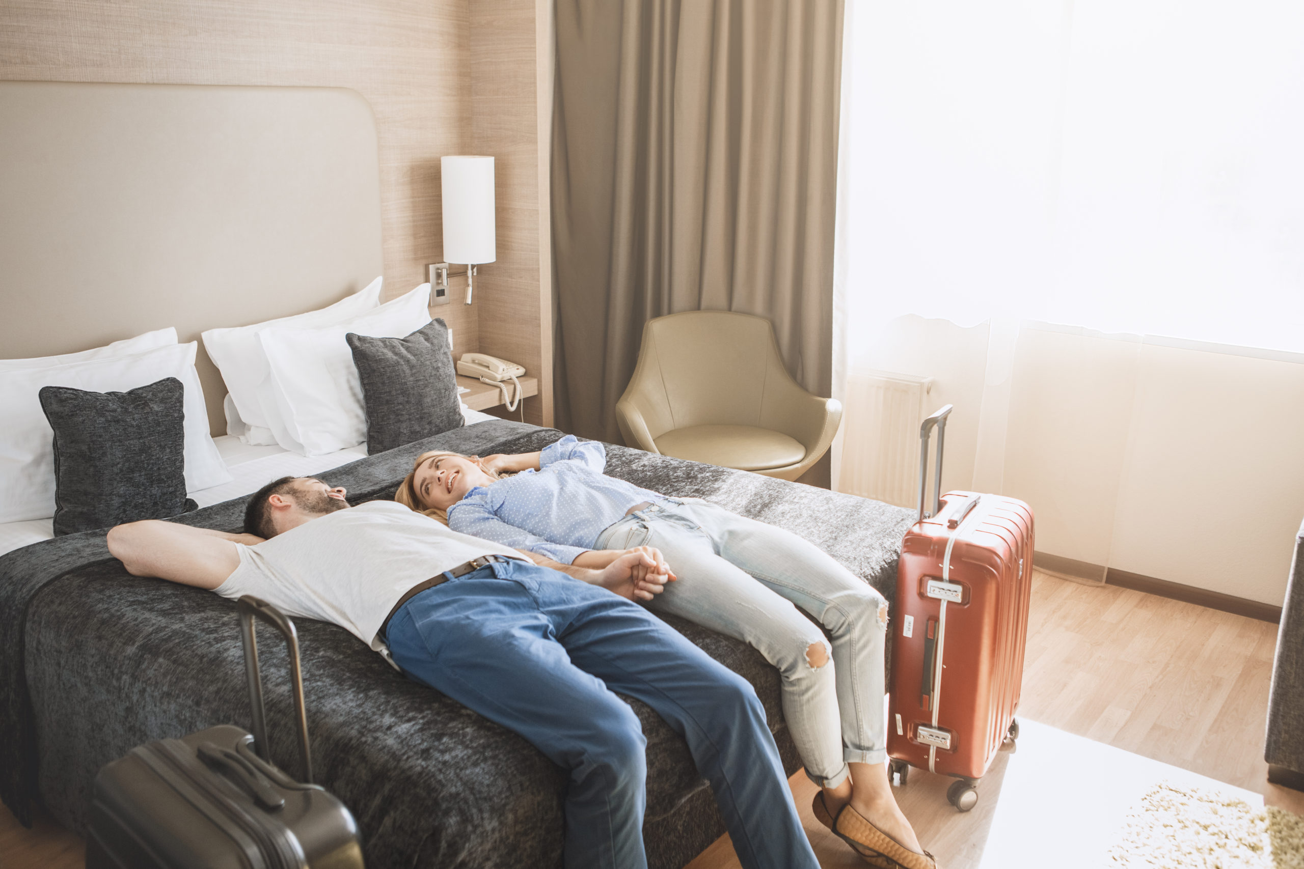 commercial-and-hospitality-Design-by-MDfxcouple-relaxing-on-bed-in-hotel-bedroom-with-air-purification-system-